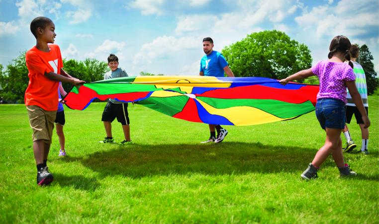 Kids and Camp Counselor play with a parachute